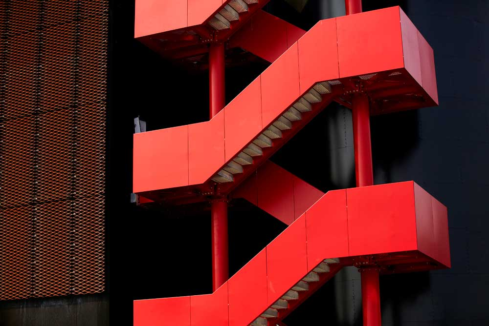 red angled external staircase and metal mesh of energy centre by airey spaces