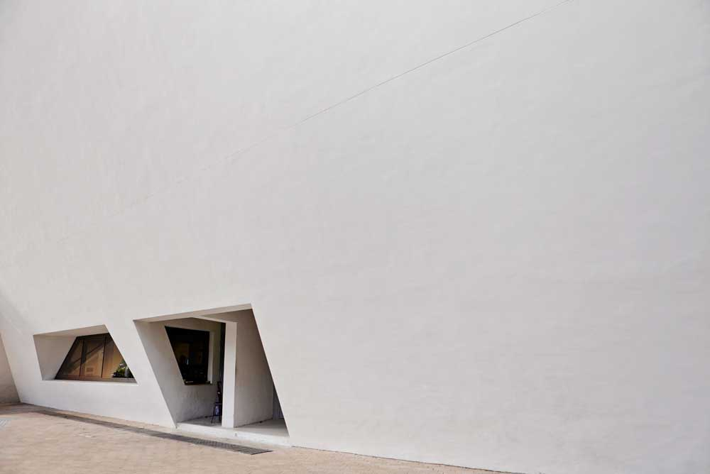 small angular window in large white wall of media centre by airey spaces