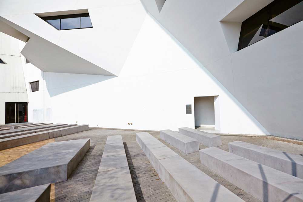 concrete seating outside white libeskind building with doorway by airey spaces