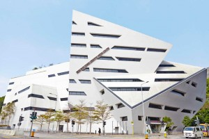 white angular libeskind building with blue sky in hong kong by airey spaces