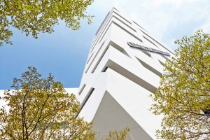 view up through green trees to white angular libeskind building by airey spaces