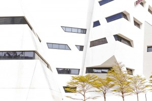 white angular daniel libeskind architect building with trees by airey spaces