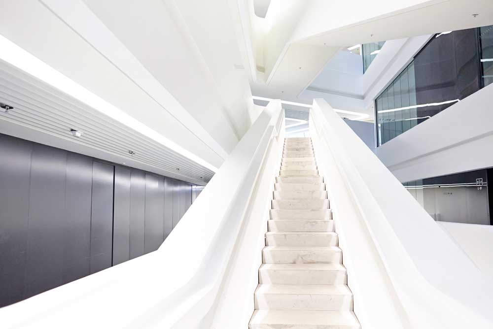 concrete and white staircase in central area of innovation tower by airey spaces
