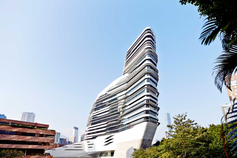 whole of white innovation tower from below with blue sky and green trees by airey spaces