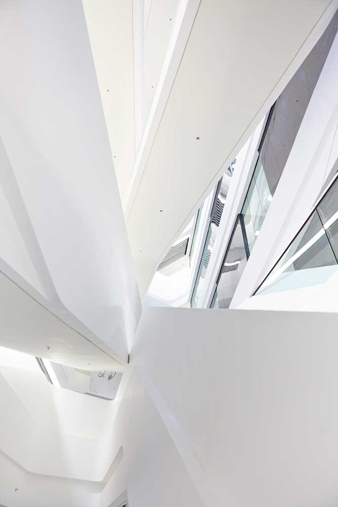 perspective view upwards of white staircase and glass rooms by airey spaces