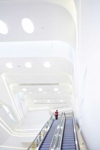entrance escalator and white curved walls of innovation tower by airey spaces