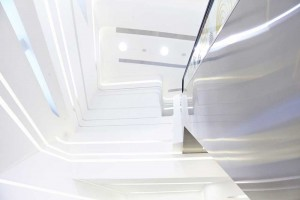metal escalator wall and white curved space of innovation tower by airey spaces