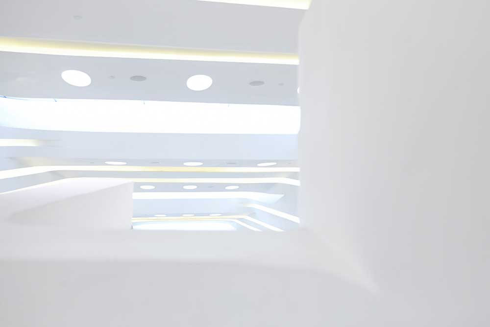 white curved walls and lighting at entrance of innovation tower by airey spaces