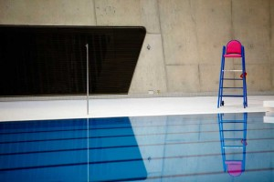 pink and blue lifeguard chair next to swimming pool of aquatic centre by airey spaces