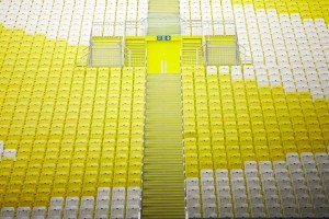 yellow and white plastic seats in london aquatic centre for olympics by airey spaces