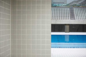 looking out from changing room to swimming pool with empty seats at aquatic centre by airey spaces