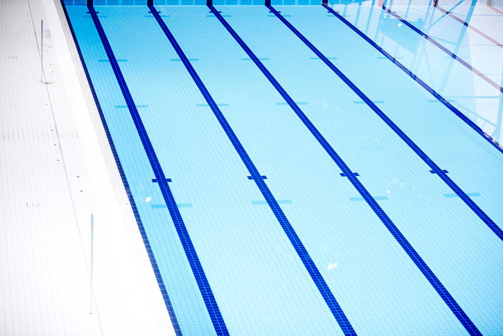 swimming lanes with blue stripes at london aquatic centre by airey spaces