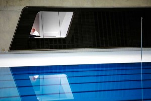 man in poolside office next to swimming lanes of london aquatic centre by airey spaces