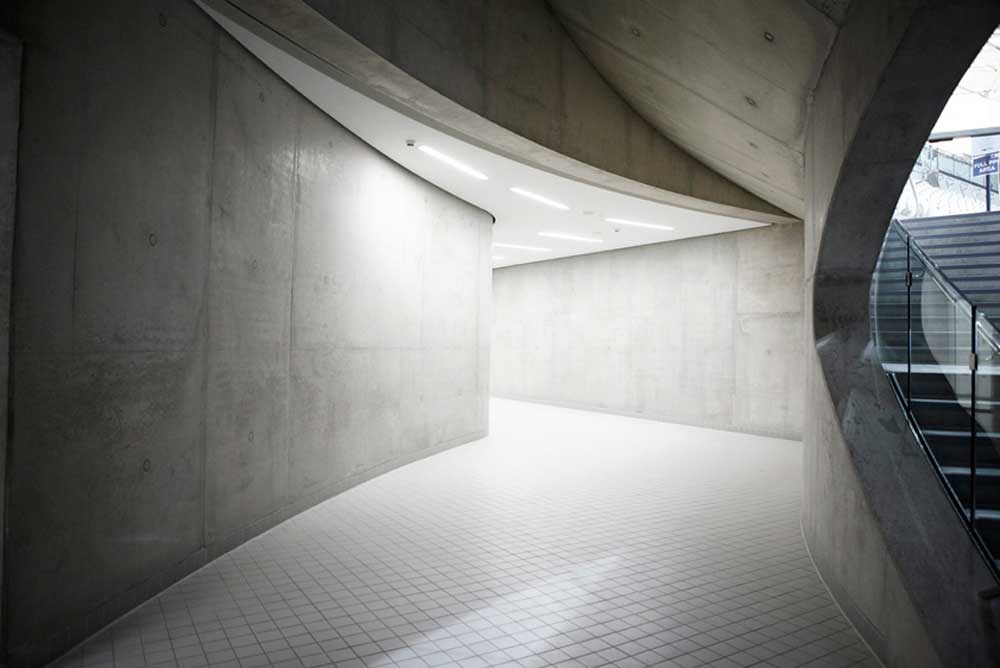 concrete and tile corridor with lighting and stairs at aquatic centre by airey spaces
