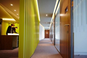 corridor of meeting rooms and two people in reception of modern office by airey spaces