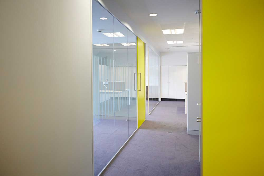 glass room office with luminous yellow wall by airey spaces