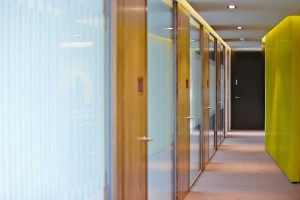 office hallway with glass doors and yellow wall by airey spaces