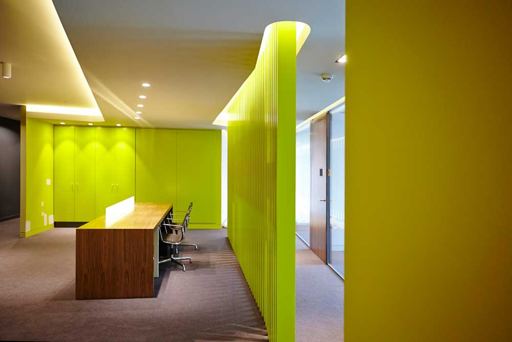 luminous green and yellow office reception area by airey spaces