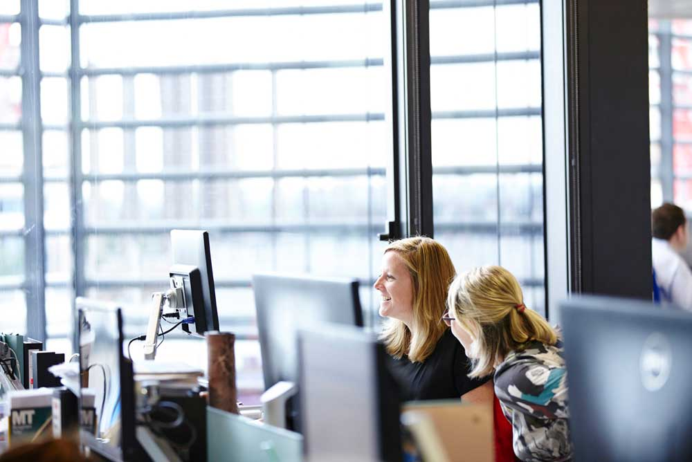 women looking at computer screen in light london office space by airey spaces