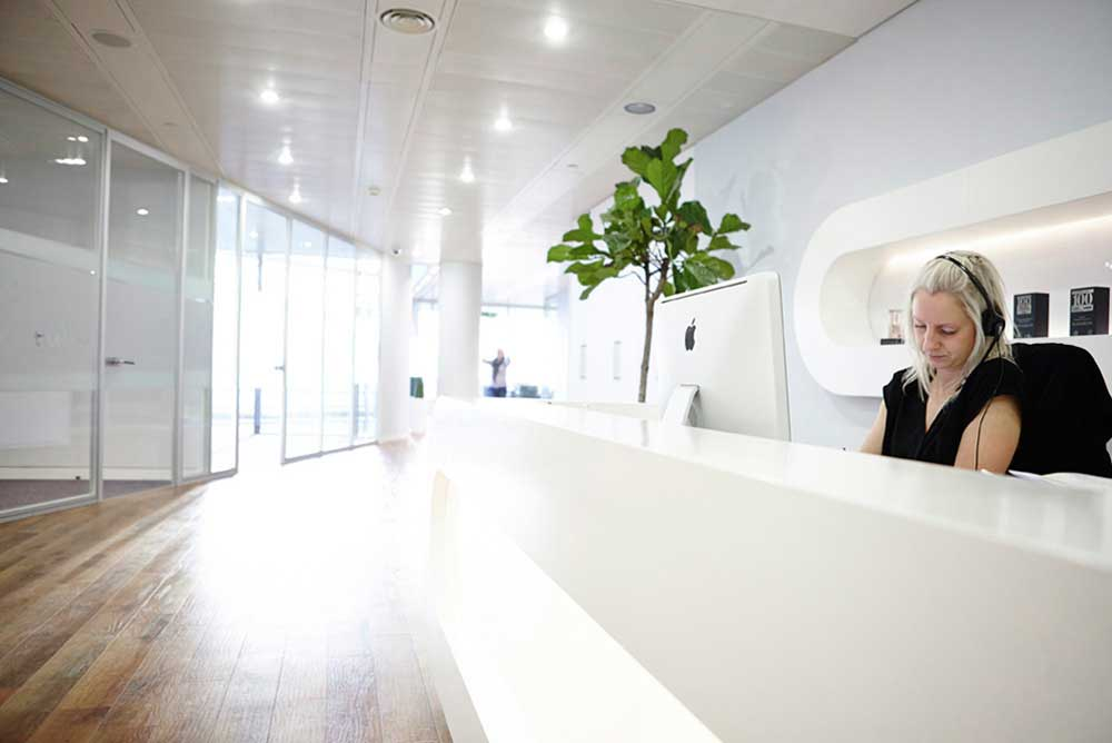 white reception area with woman at computer in london office by airey spaces