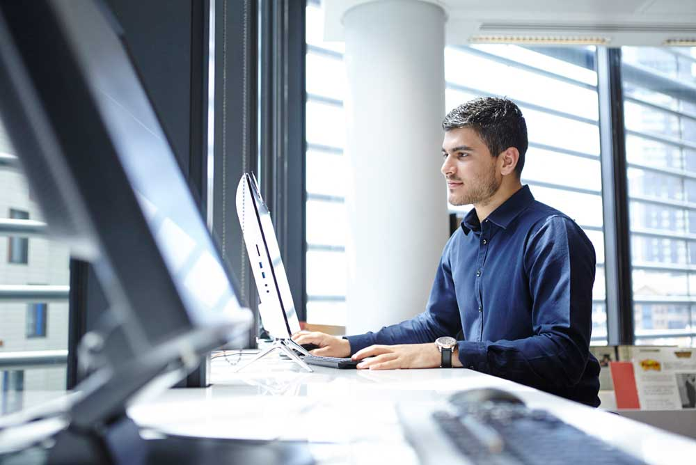 man working at computer in light london office space by airey spaces