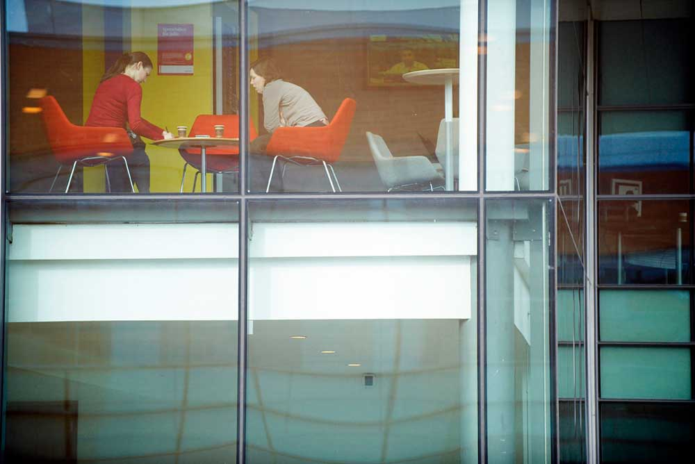women in red chairs having meeting in glass office view in by airey spaces