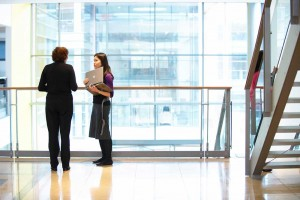 women with computer meeting in glass atrium of office by airey spaces