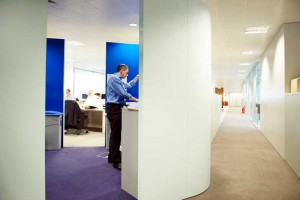 man at photocopier machine in office pod and white corridor by airey spaces