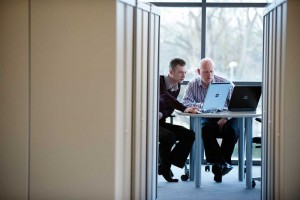 two men at computers in glass office through cupboards by airey spaces