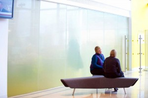 large glass wall with yellow two women sitting talking modern offices by airey spaces
