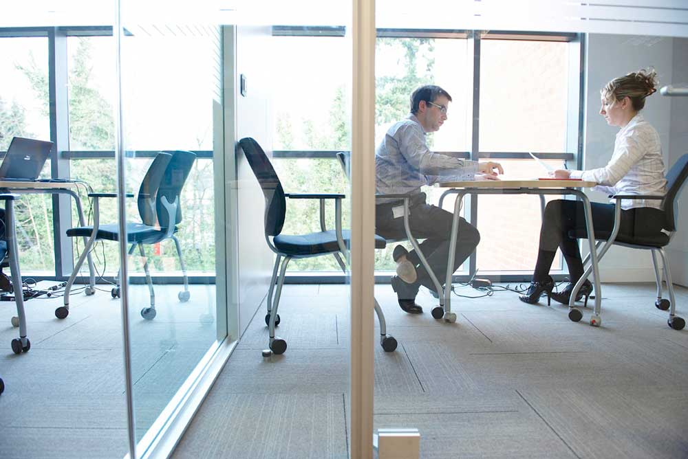view through glass of meeting rooms with woman and man in discussion by airey spaces