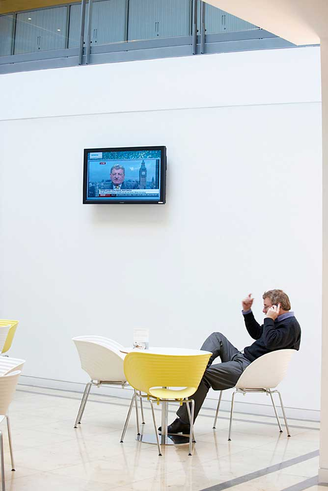 man sitting in white chair with tv in office area by airey spaces