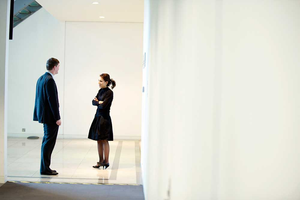 girl in black and business man talking in hallway of open plan office space by airey spaces