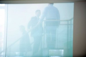 business men meeting on the stairs through frosted glass in office by airey spaces