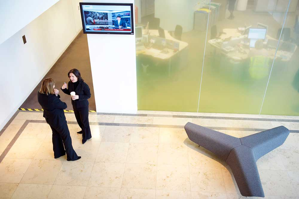 two women in black taking in open office area from above by airey spaces