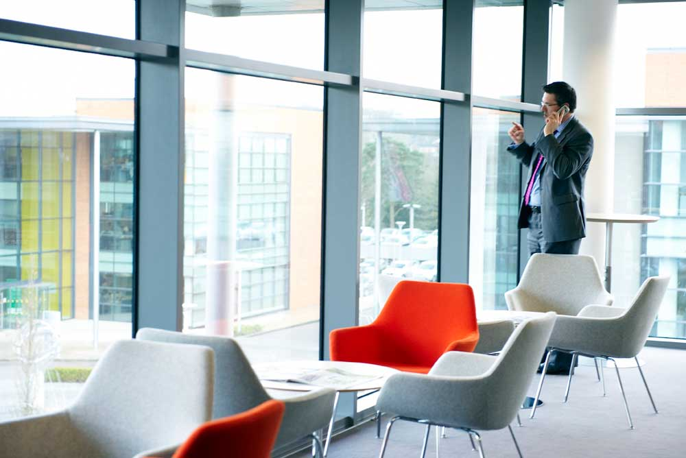 business man in suit on telephone in glass area looking out by airey spaces