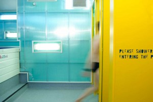 man entering yellow shower cubicle in swimming pool centre by airey spaces