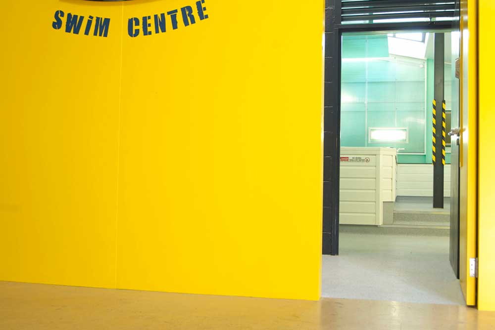 yellow wall and door into swimming centre by airey spaces