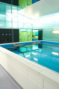 current swimming pool with mirror ceiling and black lockers by airey spaces