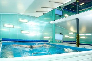 man swimming in current pool and turquoise wall in swim centre by airey spaces
