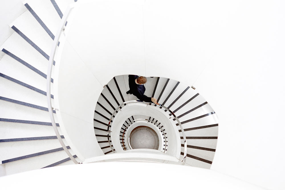 black and white spiral staircase with man ascending by airey spaces