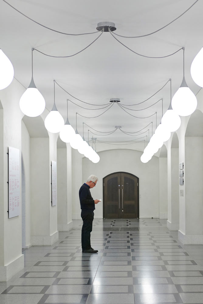 person looking at guide in tate britain with white lights by airey spaces