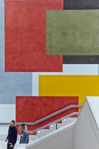 people on staircase of tate britain with art work by airey spaces