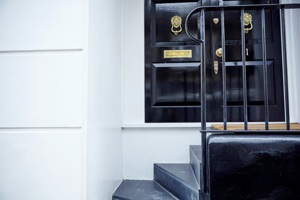 black front door and iron work on London house by Airey Spaces