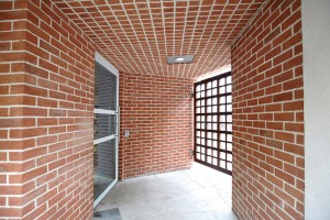 geometrical red brick building and metal gate in art gallery by Airey Spaces