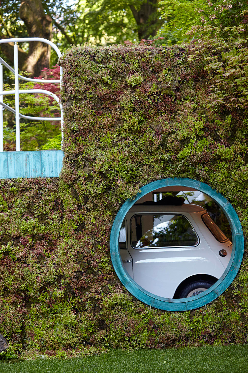 round window in moss wall showing mini car by airey spaces