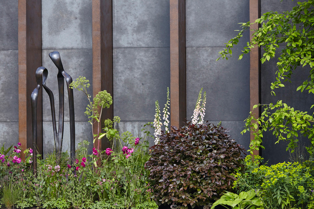 concrete and metal wall with sculptures and plants by airey spaces