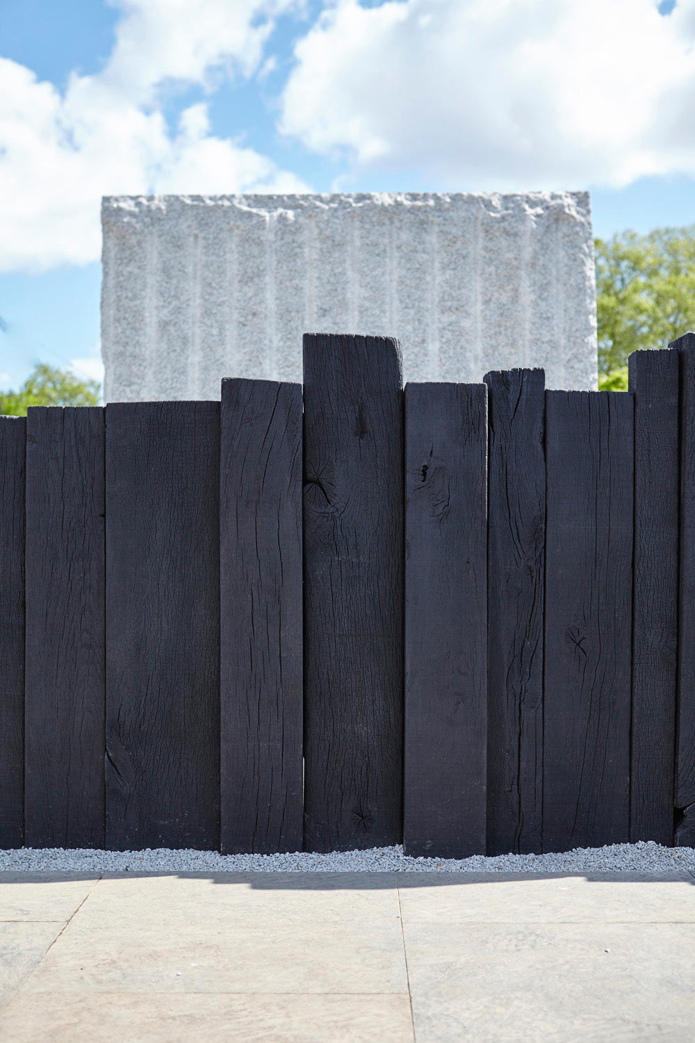 black wooden fence and white granite block by airey spaces