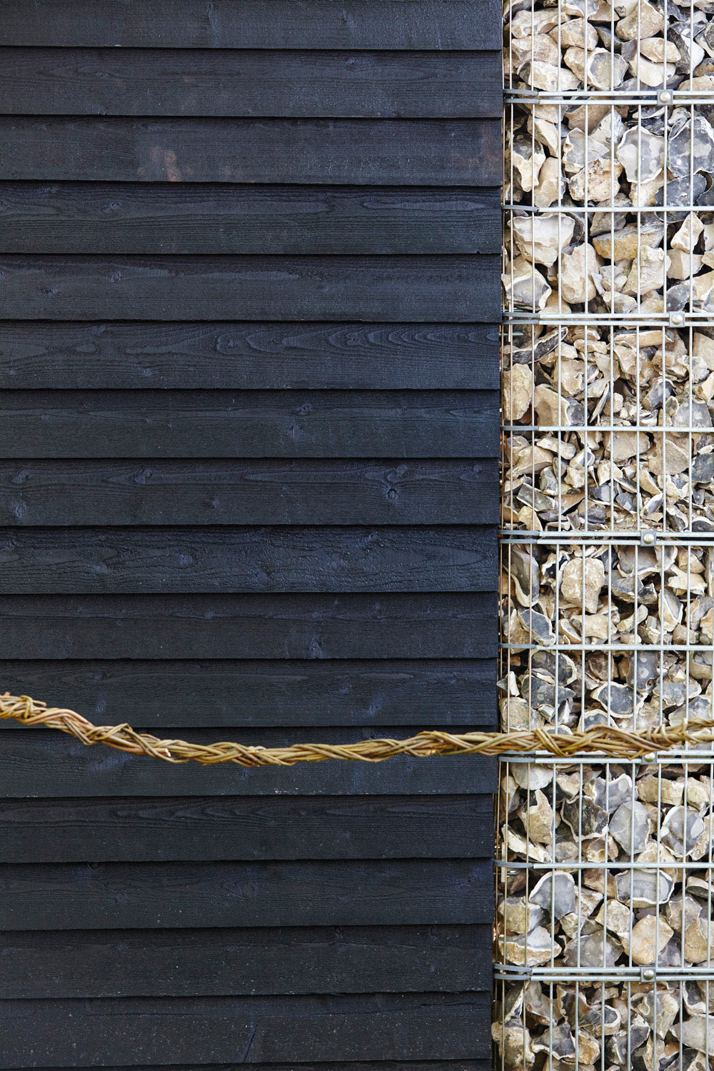 black wooden fencing and flint in cages by airey spaces