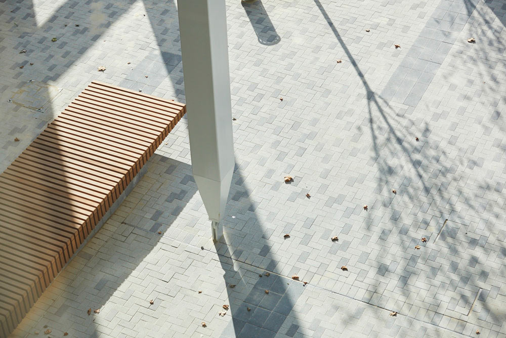 wooden bench and shadows on grey brick plaza by Airey Spaces